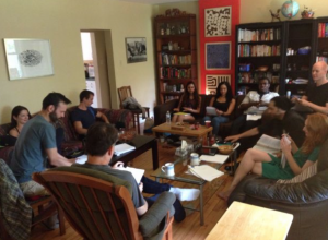 8 -10 people read from scripts while sitting around a coffee table