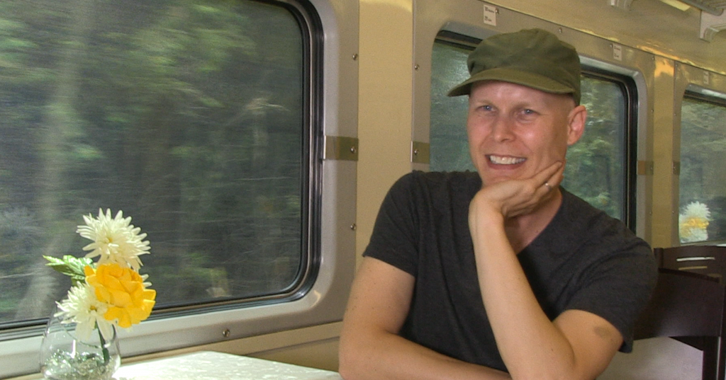 Tate sitting at a table on the train