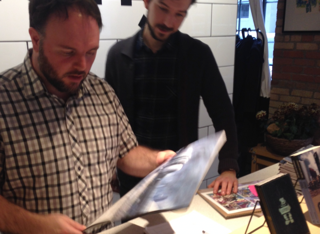 Two men look at the FALLEN TORONTO calendar